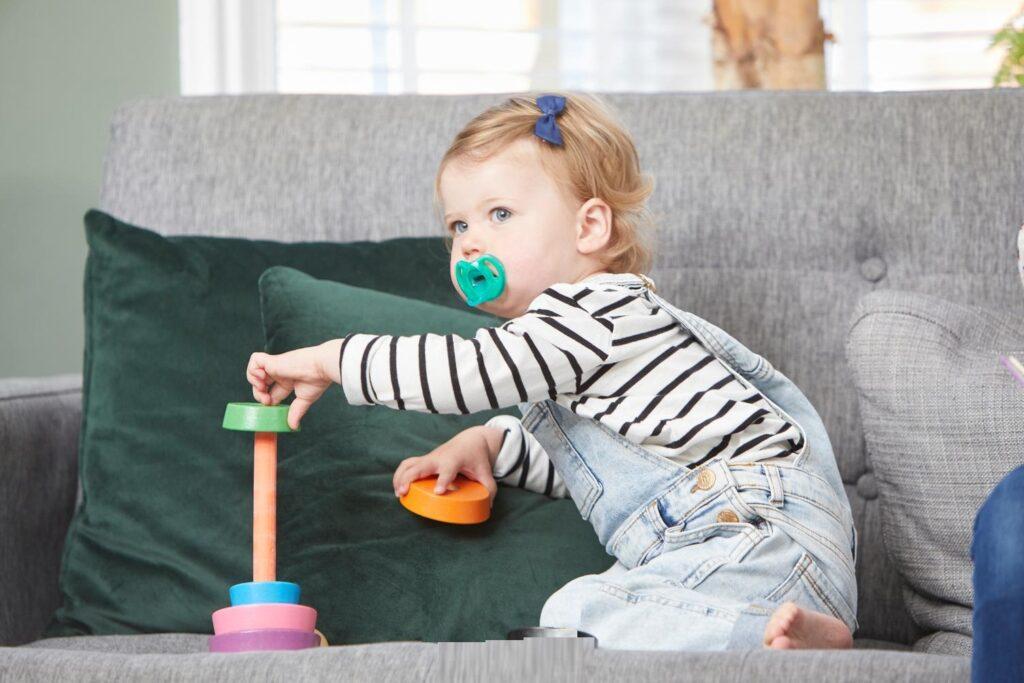 bé ngậm đồ chơi vào miệng